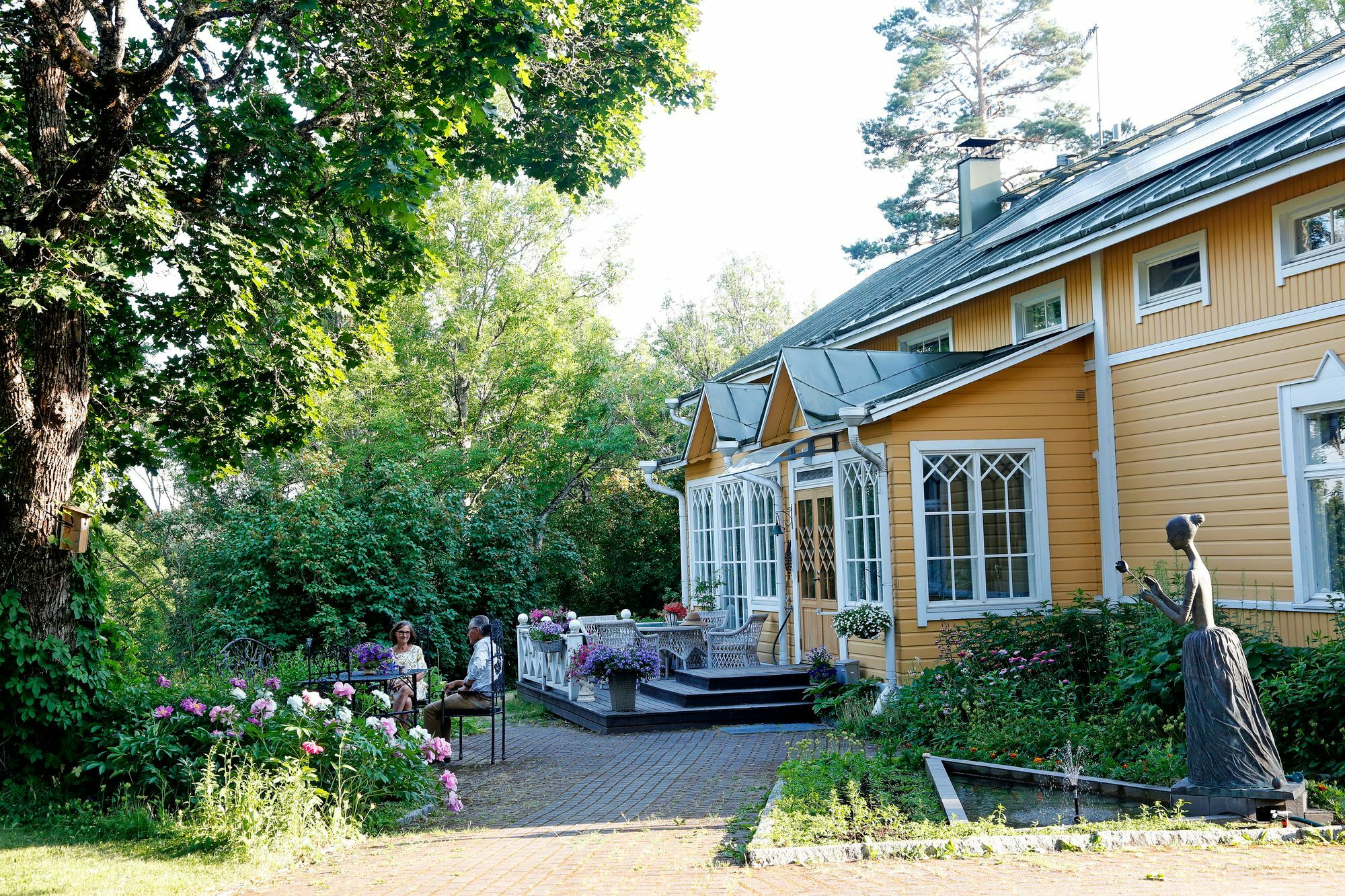 In front of the house there is a living group surrounded by flowers and art.