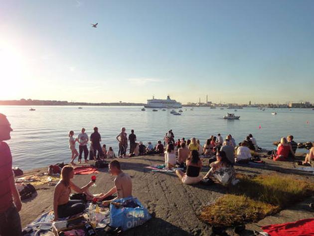 Ihmisiä viettämässä juhannusta Helsingin Pihlajasaaressa