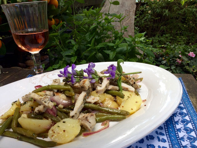 Kalkkuna-peruna-papusalaattia lautasella ja rosé-viiniä lasissa