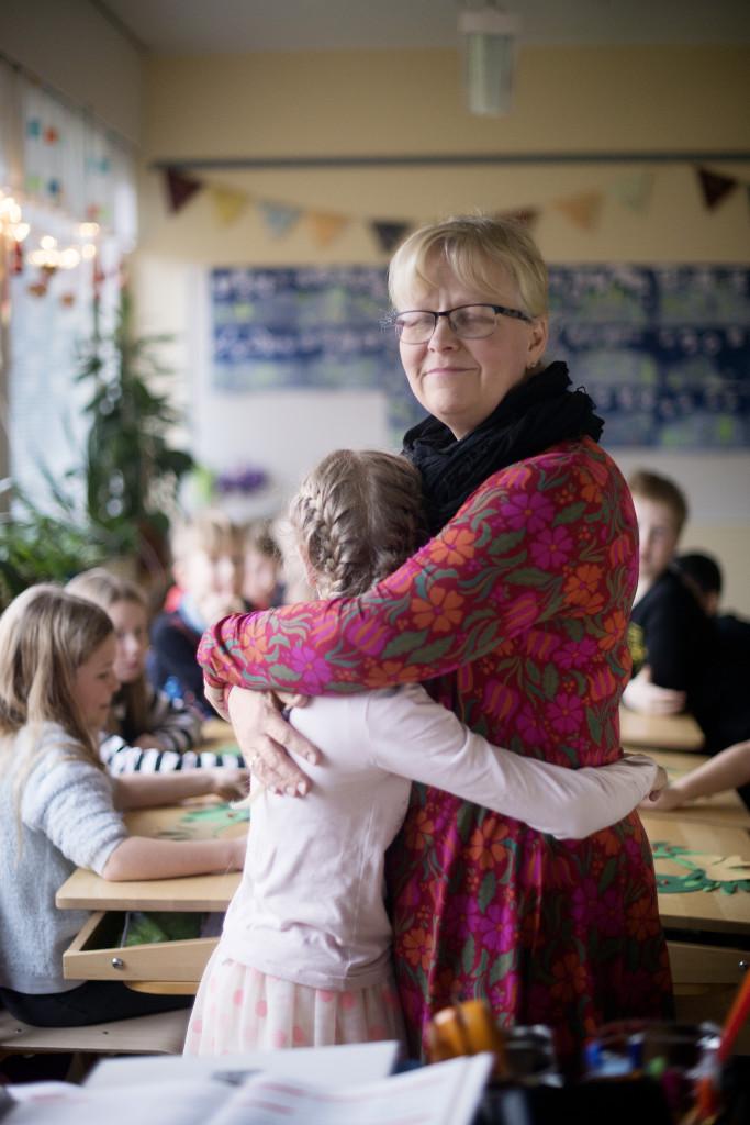 Opettaja Päivi Salminen halaa oppilastaan luokassa.