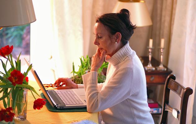 Varttunut nainen tutkii tietokonetta