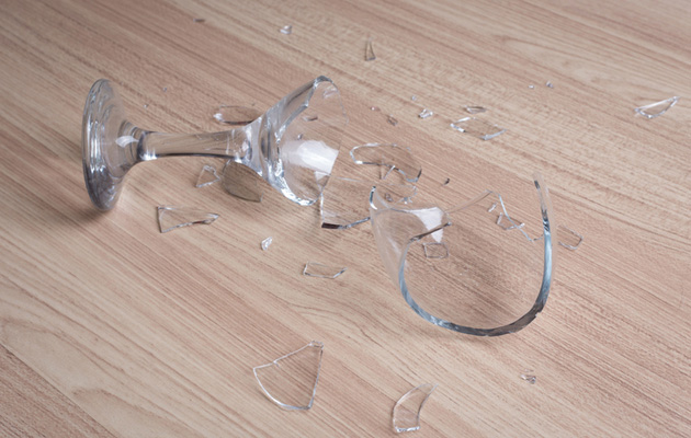 Rikkoutunut viinilasi sirpaleina lattialla