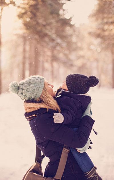 Äiti ja lapsi lumisessa maisemassa