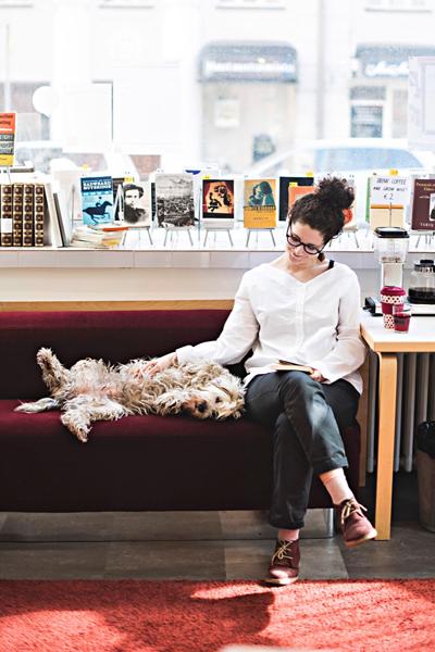 Nainen lukemassa kirjaa ja silittämässä koiraa