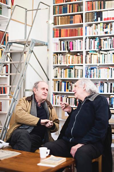Kaksi vanhaa miestä keskustelemassa kahvikupposen ääressä.