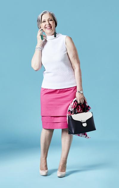 Sirkka Kuula ja pinkki hame yhdistettynä vaaleaan lyhythihaiseen paitaan sekä mustavalkoiseen nahkalaukkuun