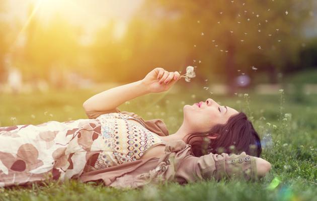Nainen unelmoi niityllä.