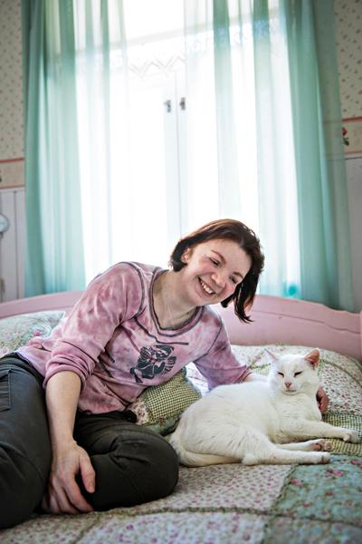 Sirpa Saarinen valkoisen kissansa vieressä