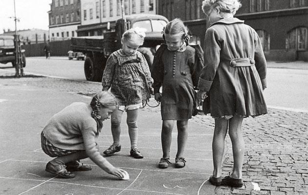 Lapset leikkii kadulla 1940-luvun kaupungissa.