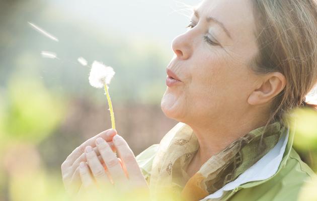 Nainen puhaltaa voikukan siemeniä
