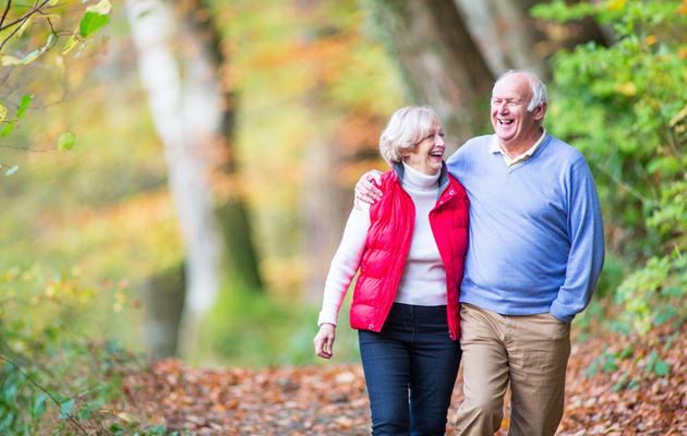Iloinen vanha pariskunta kävelyllä metsässä