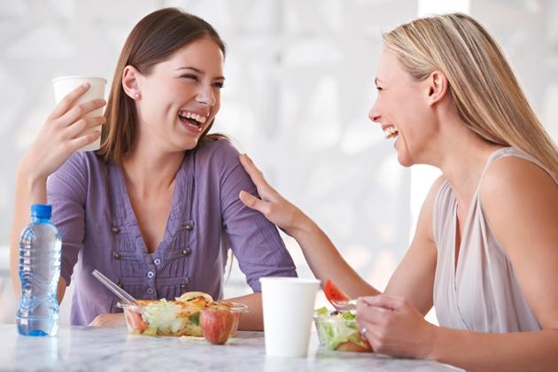 Kaksi naista syömässä eväitä työpaikalla