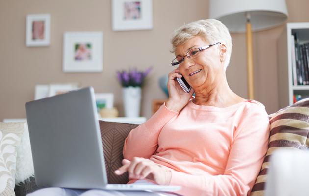 Eläkeläinen nainen työskentelee tietokoneella