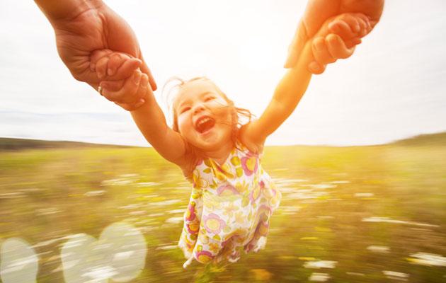 Isä pyörittää iloista lasta
