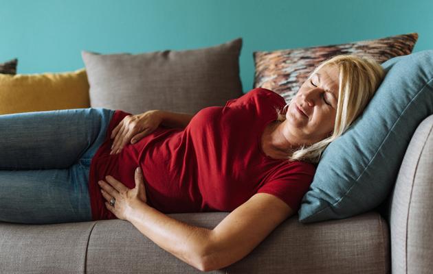 Nainen pitelee kipeää vatsaa sohvalla