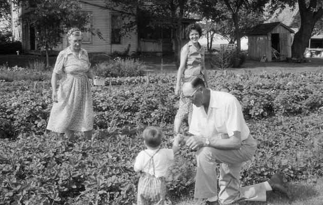 Perhe maalaistalon edessä 1960-luvulla