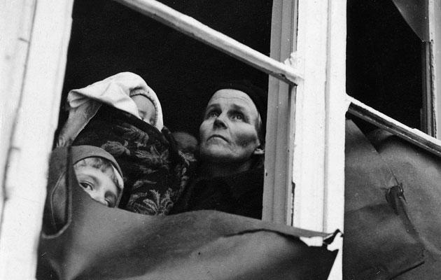 Äidin ja lasten kasvot ikkunassa entisaikaan