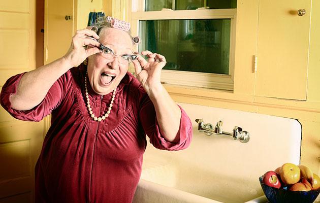 Iloinen mummo keittiössä