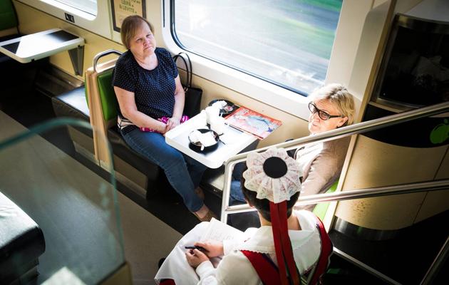 Kansallispuku puhuttaa junassa.
