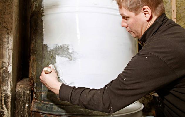 Pönttöuunia maalaamassa kirvesmies Juha Kauppila.