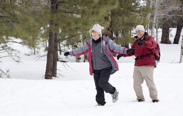 Pariskunta juoksee lumessa