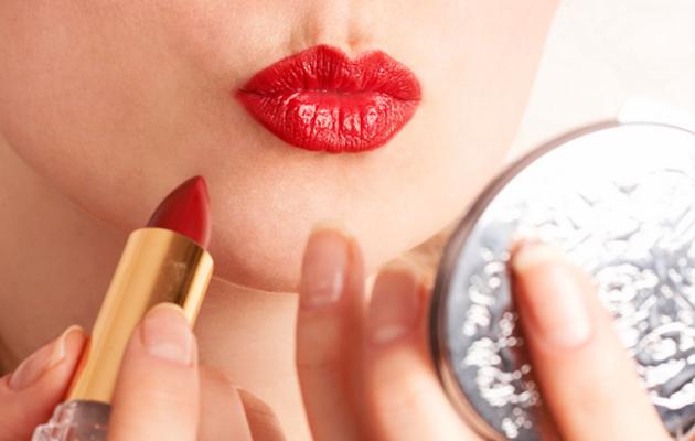 Nainen laittaa punaista huulipunaa.