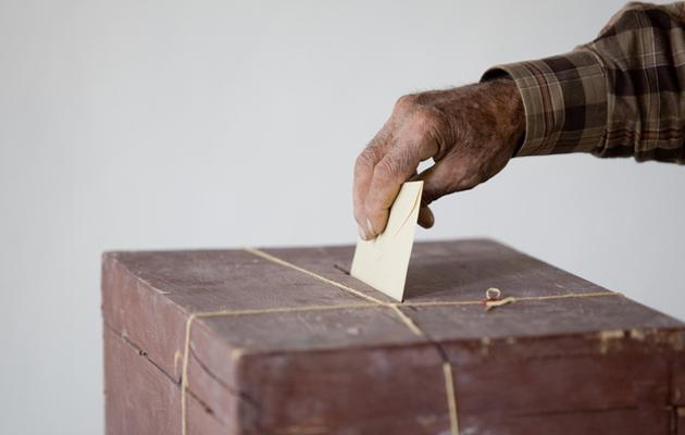 Käsi laittaa äänestyslipukkeen vaaliuurnaan