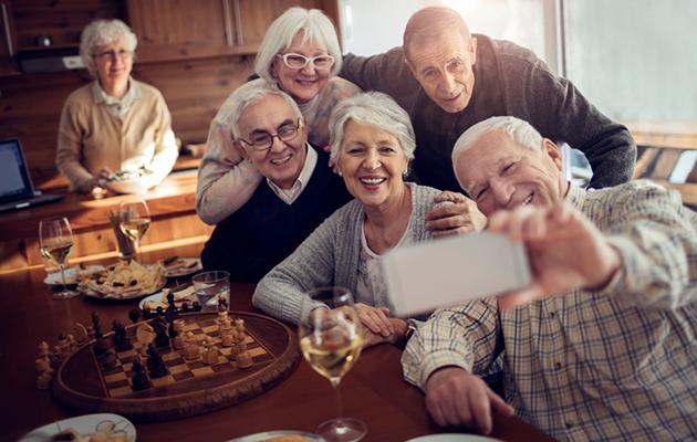 iloiset seniorit pelaavat yhdessä ja ottavat selfien