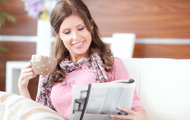 nainen lukee lehteä