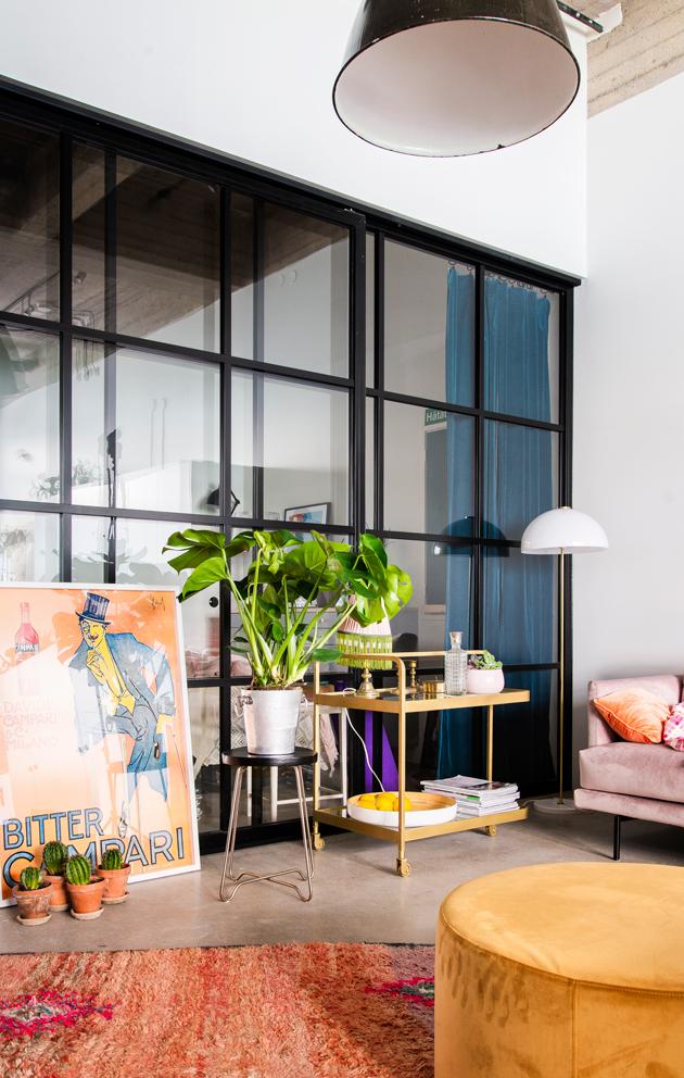 Pinkki sohva ja okran värinen rahi tuovat teollisuushenkisen kodin sisustukseen naisellisuutta.