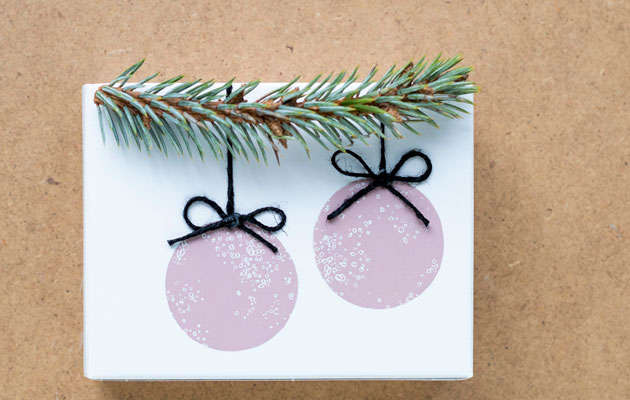 Joululahjojen paketointi, joulupallot ja kuusenoksa.