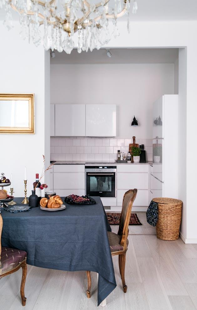 Vaaleasävyisessä avokeittiössä on marmoritaso ja mustat seinävalaisimet. Kodissa on myös antiikkia ja kierrätettyjä huonekaluja.