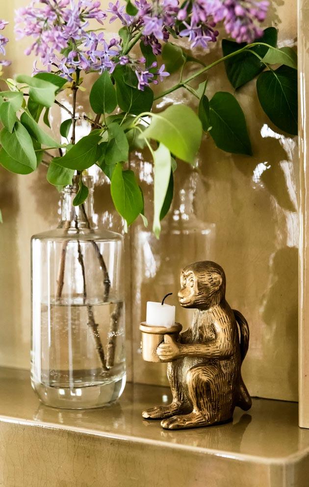 Sireeninoksa lasipullossa ja hauska kynttilänjalka viihtyvät kakluuninreunalla.