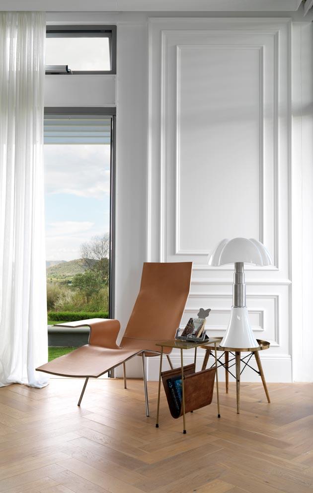 Koti on sisustettu maanläheisellä väripaletilla, jota valkoinen raikastaa. Lattiasta kattoon ulottuvista ikkunoista aukeaa näkymä savannille.