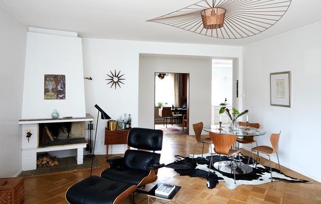 Ullan ja Kallen iso olohuone on täynnä designklassikoita. Vertigo-valaisin kokoaa sisustuksen yhteen ja on itsessään kuin kattoon ripustettu veistos. Kuva: Krista Keltanen