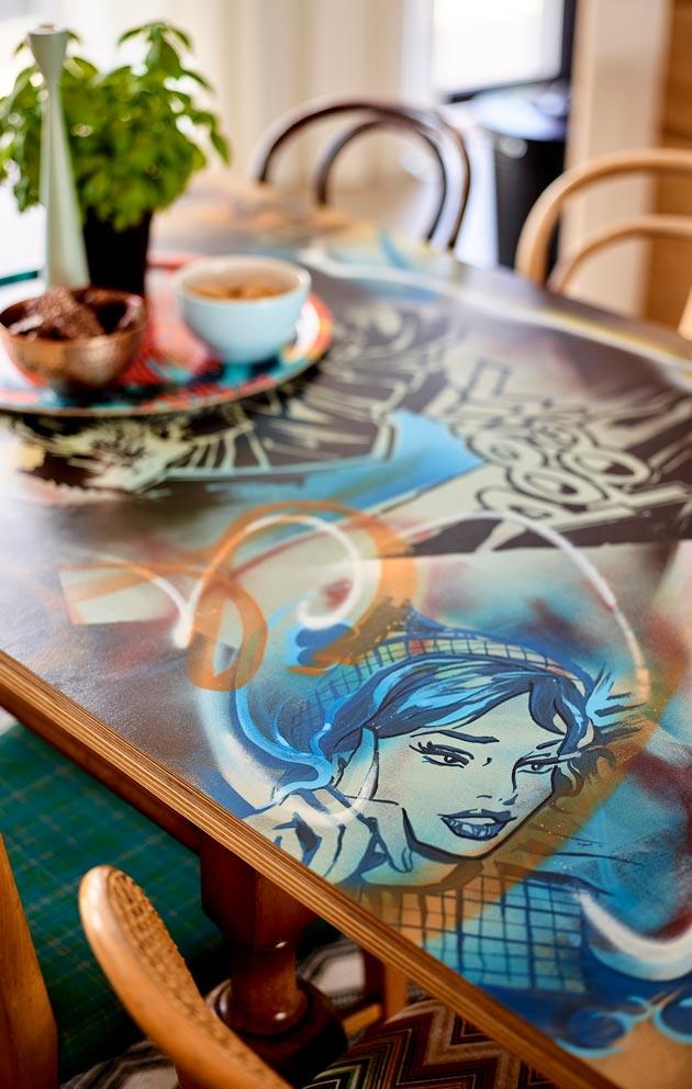 sisustuksen rohkeus ja värikkyys tulee esiin myös ruokapöydän kannessa. Tilaustyö on Pete Pihlajamaan maalaama.