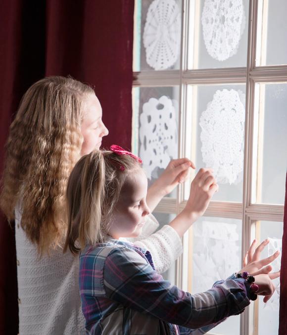 lumihiutaleet paperista ikkunaan kiinnitettyinä