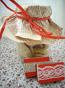 Ruokalahja, keksipurkki, sanomalehtikääre, pitsillä somistettu kortti